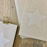 Karte mit weißem Stern auf Kraftpapier und Muster